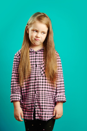 Frustrated girl with sad face on isolated blue background. Stock Photo