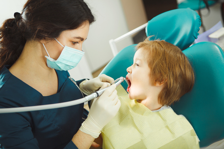 Dentist preparing drill tooth to child, little patient obediently opened his mouth, sitting on chair.