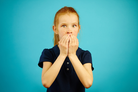 Red haired girl with big eyes of fear covered mouth with hands against blue background. Stock Photo