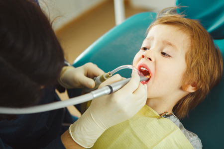 Dentist drills tooth to small boy, calm child in doctors chair suffers pain.