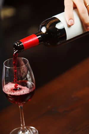 Waiter pouring red wine into wineglass. Sommelier pours alcoholic drink Stock Photo