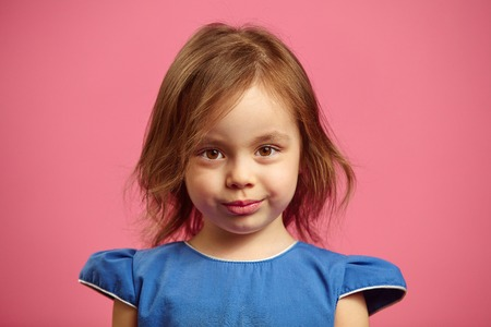 Close up portrait of charming little girl with serious look on pink isolated.
