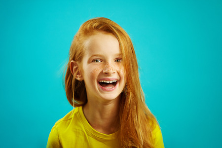 Sincere laughter of children girl with red hair on blue isolated. Happy child expresses a sincere emotion. 免版税图像