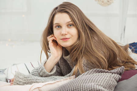 Beautiful woman no makeup lying on pillow in grey knitted sweater, long straight hazel hair. Young lady looking at camera, background is blurred. 版權商用圖片