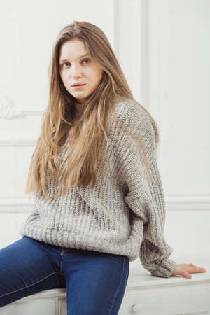 No makeup woman with wild long hair sitting on white furniture on background of wall. Just wake up lady in cosy grey warm sweater looking at camera