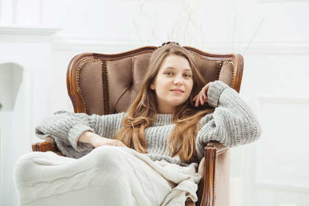 Woman with long hair and green eyes sitting in vintage wooden armchair with blanket on her knees near white background