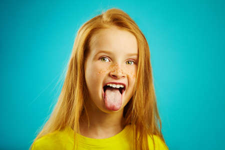 Horizontal shot of child girl with expressive eyes and large eyes stuck her tongue out, mouth wide open, shows a mischievous nature. Spoiled child on isolated blue background.
