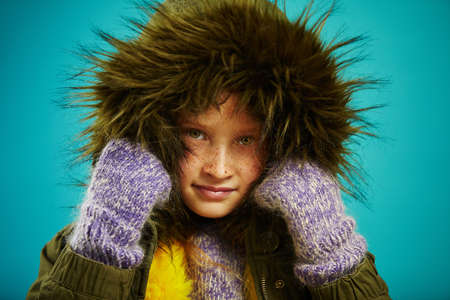 close up portrait of little girl in warm autumn jacket with fur hood in green and mittens, shot on blue isolated background. Winter clothes for children. 版權商用圖片
