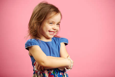 Children's beautiful girl with shyness stands on pink isolated background, wears fashionable dress of blue color, expresses sincere emotion. 版權商用圖片