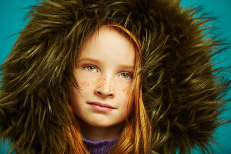 Studio close-up portrait of cute redheaded child girl with freckles hid in large hood jacket. Beautiful kid in winter clothes.