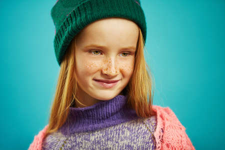 close up image of cute girl in winter sweater and hat on blue isolated background. 版權商用圖片