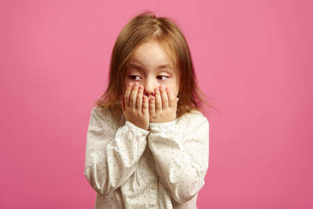 Little girl covered her mouth with hands, looking guilty in the side, regrets what she said, feels conscience for bad word, female child feels conscience.