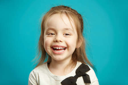Horizontal shot of joyful kid girl with charming smile, sincerely laughs, expresses cheerful mood and pleasure, emotional children portrait over blue isolated background.