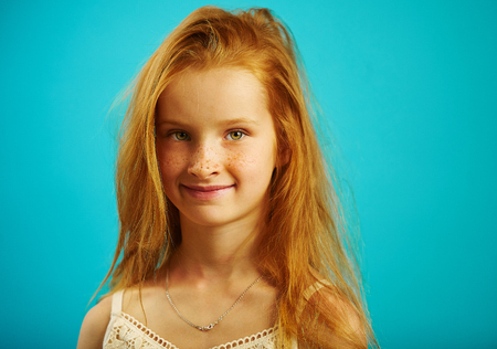 Red haired girl with sincere look on blue background.
