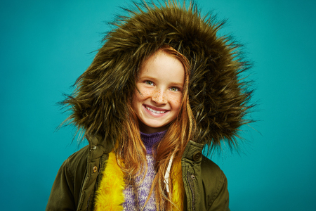 Joyful children girl in demi season winter jacket isolated on blue background. Smiling teenage child expresses sincere positive emotions, wears warm clothes, waiting for approach of winter.