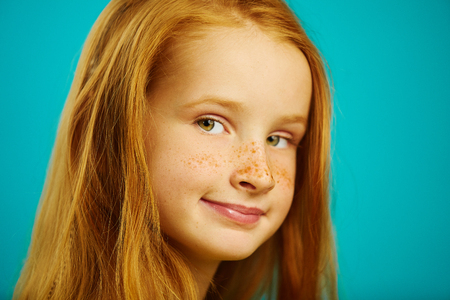cute ten year old redheaded girl on blue isolated background, close-up shot of beautiful child with freckles.