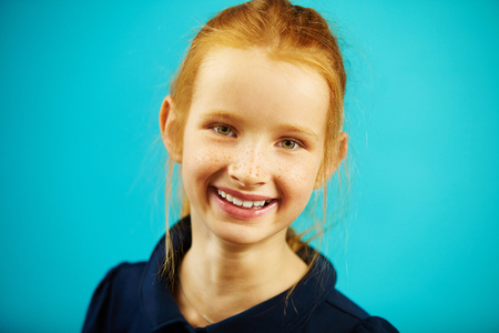 Portrait of cheerful redheaded school girl of seven years old on blue isolated background. Joyful child with genuine sincere emotions experiences happy moments.