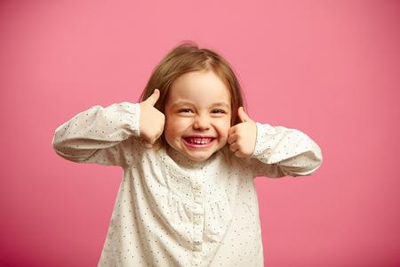 Lustige Aufnahme eines kleinen Mädchens mit den Daumen nach oben Standard-Bild