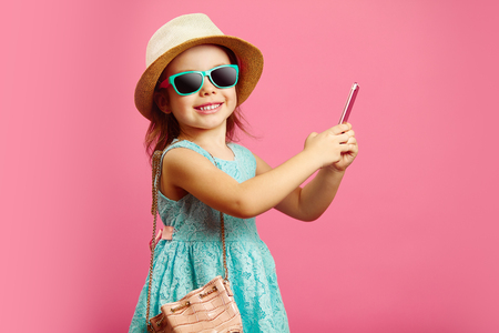 Beautiful little girl with charming smile looks at you, dressed in fashionable blue dress, wearing a beach hat and sunglasses, holding a phone, standing on isolated pink.