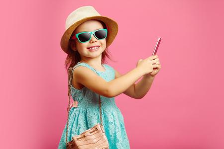 Schönes kleines Mädchen mit charmantem Lächeln sieht dich an, gekleidet in modischem blauem Kleid, trägt einen Strandhut und eine Sonnenbrille, hält ein Telefon und steht auf isoliertem Rosa.