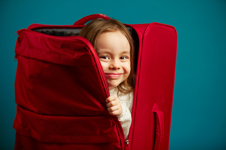Little girl looks out of red suitcase, portrait of cheerful child on blue isolated background.