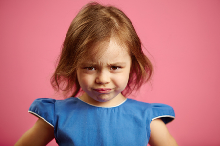 Portrait of sad little girl on isolated pink.