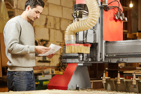 Man sets the program to the CNC machine. Device with numerical control. Stok Fotoğraf