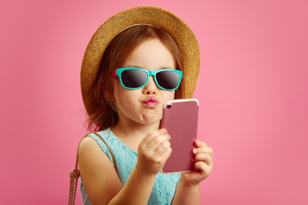 Funny little girl makes a selfie portrait on phone, pulls her lips to the camera, wears a straw hat and sunglasses, dressed in blue dress, stands on isolated pink.