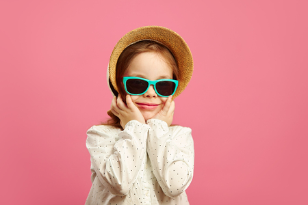 e85cacaa23be5e Cute little girl in beach hat, sunglasses and white jacket, cute smiles,  stands