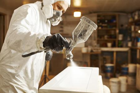 Man in respirator mask painting wooden planks at workshop. Reklamní fotografie