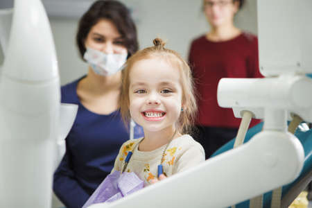 Cheerful kid with broad smile after painless teeth polishing procedure sits in comfortable chair at modern dentist office with mother and doctor in ask who stand behind.