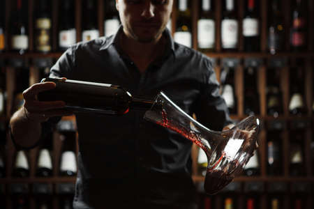 Sommelier pouring fine red wine in decanter, man holding bottle with label, cellar and collection of containers on wooden shelves, closeup of dim dark photo and handsome man, backlight shot of barthender on shelf background