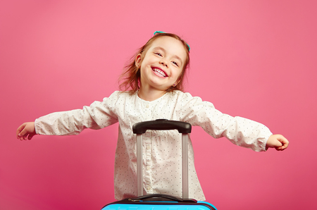 Cute little girl extended arms, depicts a plane, smiling happily, stands near suitcase on isolated pink. Banco de Imagens