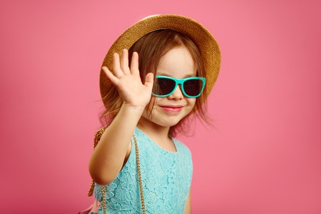 1292b022a7b8b2 Little cute girl in summer hat and sunglasses waving at you,expressing joy  and happiness