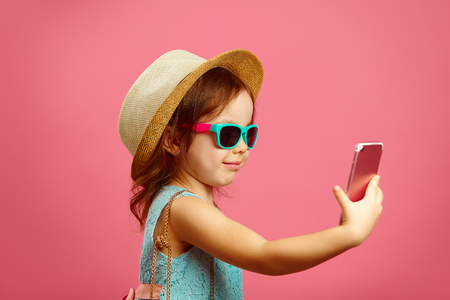 269ad6bc529442 Profile shot of little girl makes a selfie portrait on the phone, dressed  in summer