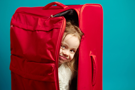 Little girl looks out of red suitcase on blue isolated background.