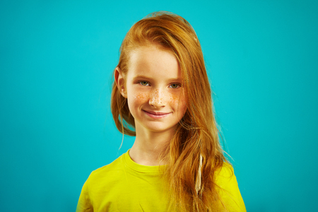 Portrait of cute seven years old girl with red hair and beautiful freckles, wears yellow t-shirt, expresses sincere emotions and honest look, has nice facial.