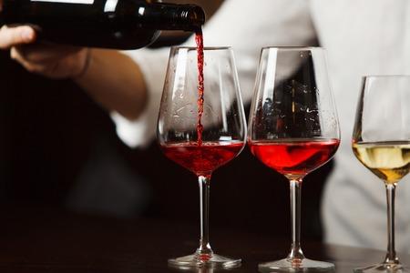 Sommelier gießt verschiedene Arten von edlem Wein ein Standard-Bild