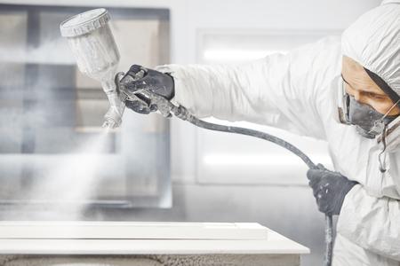 Hombre en máscara de respirador pintando tablones de madera en el taller.