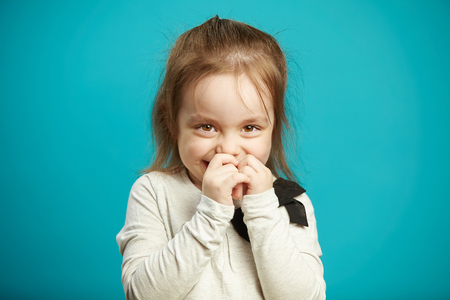 Little shy girl smiles and covers her mouth with hands, expresses embarrassment and indecision, emotional photo of children shyness on blue background.
