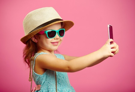4d9e0d9eab1b39 Beautiful little girl dressed in summer dress, wearing a straw hat and  sunglasses, makes