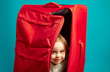 Beautiful girl hiding in red luggage bag, close-up shot on blue isolated.