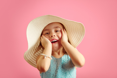 Portrait of surprised girl with open moutn, wears beach hat and beautiful blue dress, expresses joy and happiness, stands over pink isolated background.