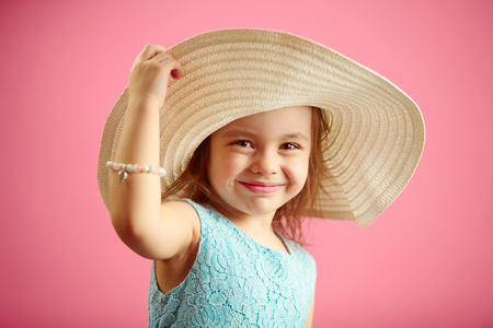 Beautiful little girl in beach hat stands over pink isolated background. Stock Photo