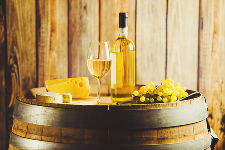 white wine on barrel with grape and cheese on background of wooden wall.