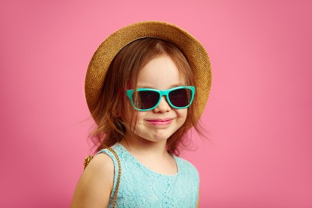 Portrait of beautiful little girl with straw hat and sunglasses, wears blue dress, stands on pink isolated.