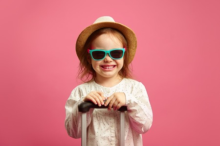 Smiling little girl in sunglasses and straw hat, holding suitcase on isolated pink, sincerely expresses joy and anticipation.