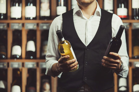 Close-up portrait of sommelier holds a bottle of red and white wine on cellar background. Varieties of alcoholic beverages.