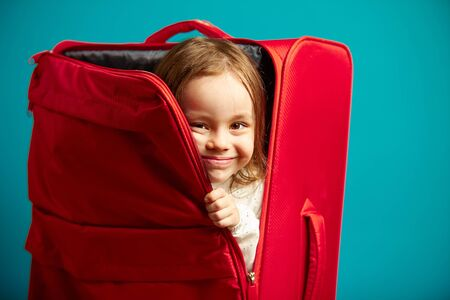 Little girl looks out of red suitcase. Portrait of happy child on isolated blue background. Фото со стока
