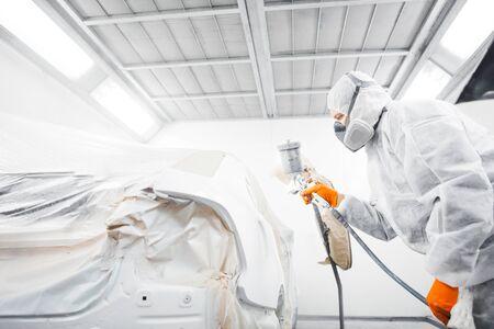 Mannelijke arbeider die een auto in een witte verfcabine schildert.